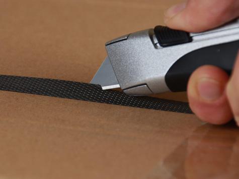 Foto Sicherheitsmesser extra sicher mit vollautomatischem Klingenrückzug für hohe Sicherheit vor Schnittverletzungen hier beim Schnitt eines Umreifungsbansbands