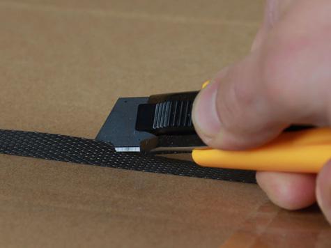Foto Sicherheitsmesser mit automatischem Klingenrückzug hier beim Schnitt von einem Umreifungband